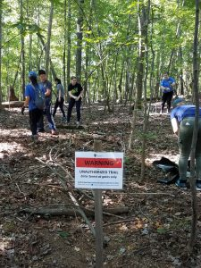 "Duke Forest volunteers brushing a trail with ""Unauthorized Trail"" signage"